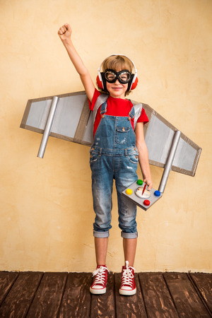 Photo pour Kid pilot playing with toy jetpack at home. Success and leader concept - image libre de droit