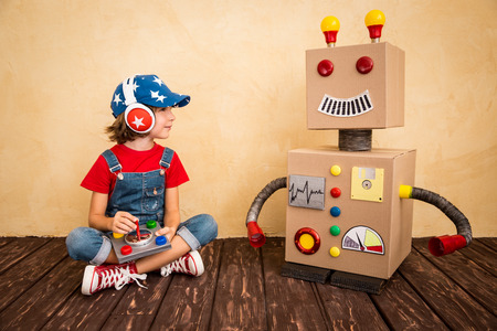 Photo pour Happy child playing with toy robot at home. Retro toned - image libre de droit