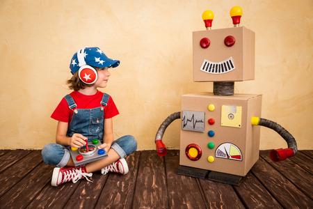 Foto de Happy child playing with toy robot at home. Retro toned - Imagen libre de derechos