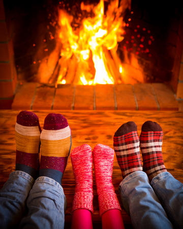 Foto de Family relaxing at home. Feet in Christmas socks near fireplace. Winter holiday concept - Imagen libre de derechos