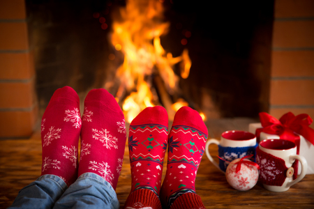 Photo pour Couple relaxing at home. Feet in Christmas socks near fireplace. Winter holiday concept - image libre de droit