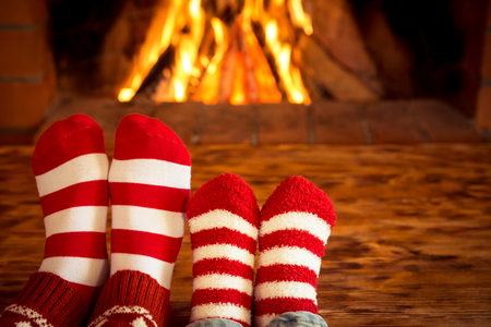 Foto de Mother and children feet in Christmas socks near fireplace. People relaxing at home. Winter holiday concept - Imagen libre de derechos