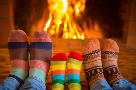Foto de Family relaxing at home. Feet in Christmas socks near fireplace. Winter holiday concept - Imagen libre de derechos