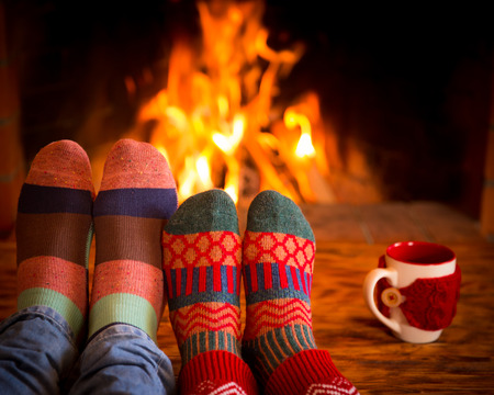 Foto de Couple relaxing at home. Feet in Christmas socks near fireplace. Winter holiday concept - Imagen libre de derechos