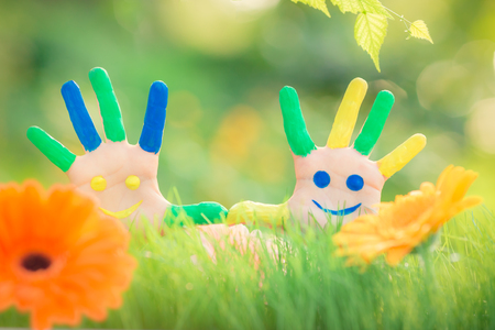 Foto de Happy child with smiley on hands against green spring background - Imagen libre de derechos
