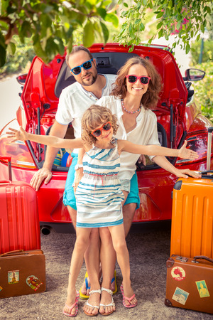 Foto de Happy family ready to trip. People standing near red car. Summer vacation and travel concept - Imagen libre de derechos