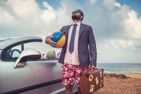 Photo for Successful young businessman on a beach. Man standing near cabriolet classic car. Summer vacations and travel concept - Royalty Free Image