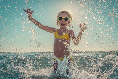 Foto de Happy child playing in the sea. Kid having fun outdoors. Summer vacation and healthy lifestyle concept. Toned image - Imagen libre de derechos