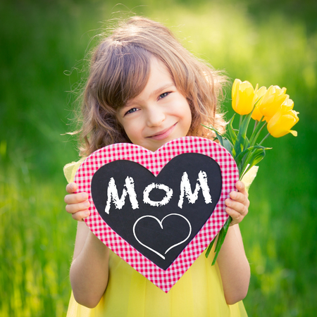 Photo for Child holding card blank and bouquet of flowers against green background. Spring family holiday concept. Mother's day - Royalty Free Image