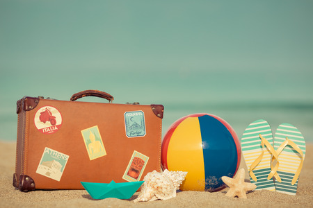 Photo for Vintage suitcase and flip-flops on sandy beach against blue sea and sky background. Summer vacation concept - Royalty Free Image