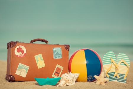 Foto de Vintage suitcase and flip-flops on sandy beach against blue sea and sky background. Summer vacation concept - Imagen libre de derechos