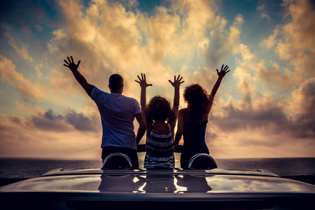 Silhouette of family relaxing on the beach. People having fun in cabriolet against blue sky background. Summer vacation and travel concept