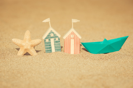 Toy house on sandy beach against blue sea and sky background. Summer vacation concept