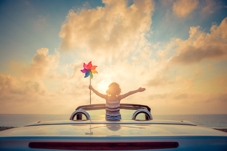 Silhouette of child relaxing on the beach. Person having fun in cabriolet against blue sky background. Summer vacation and travel concept