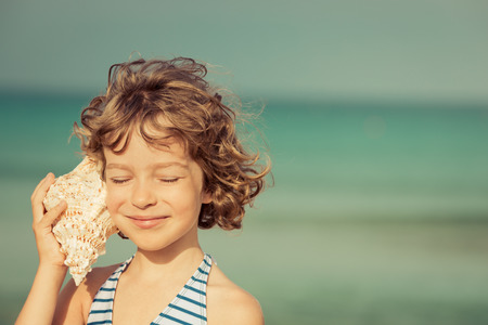 Foto de Child relaxing on the beach against sea and sky background. Summer vacation and travel concept - Imagen libre de derechos