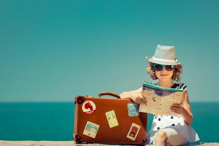 Foto de Child with vintage suitcase and city map on summer vacation. Travel and adventure concept - Imagen libre de derechos