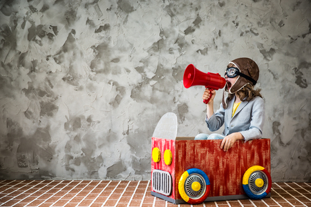 Foto de Child driving a car made of cardboard box. Kid having fun at home. Travel and vacation concept - Imagen libre de derechos