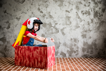 Photo pour Child driving in a car made of cardboard box. Kid having fun at home. Success and winner concept - image libre de droit