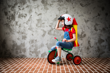 Photo pour Child with cardboard rocket riding a retro bicycle. Kid having fun at home. Travel and vacation concept - image libre de droit