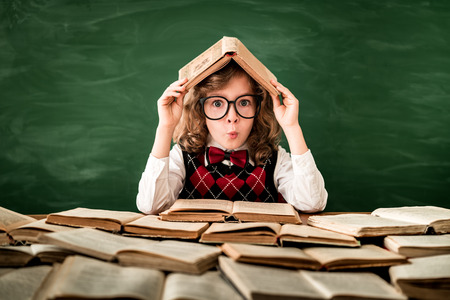 Photo pour Back to school. Schoolchild in class. Happy kid against green blackboard. Education and creativity concept - image libre de droit