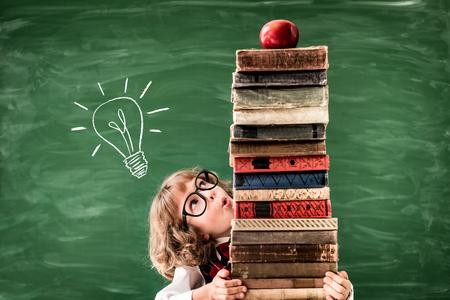 Photo pour School child in class. Happy kid against green blackboard. Education concept - image libre de droit