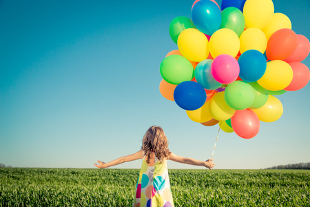 Photo pour Happy child playing with balloons outdoor. Kid having fun in spring field - image libre de droit