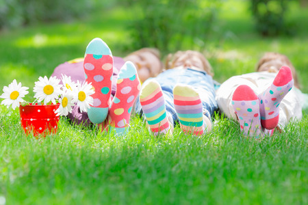 Photo for Group of happy children playing outdoors. Kids having fun in spring park. Friends lying on green grass - Royalty Free Image