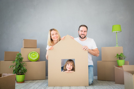 Photo for Happy family playing into new home. Father, mother and child having fun together. Moving house day and real estate concept - Royalty Free Image