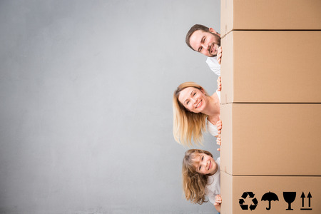 Photo pour Happy family playing into new home. Father, mother and child having fun together. Moving house day and real estate concept - image libre de droit
