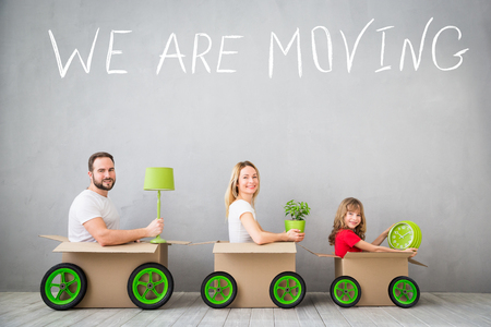 Foto de Happy family playing into new home. Father, mother and child having fun together. Moving house day and express delivery concept - Imagen libre de derechos