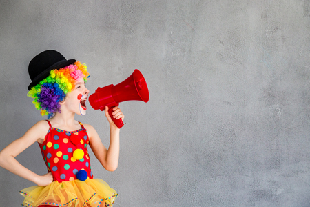 Photo for Funny kid clown. Child speaking with megaphone. 1 April Fool's day concept - Royalty Free Image