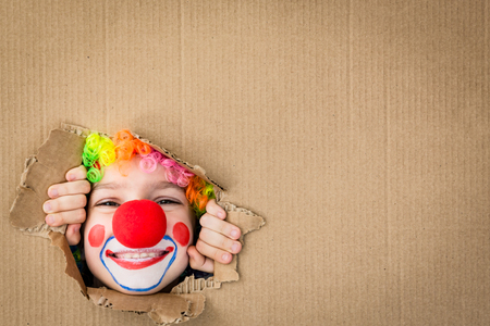 Foto de Funny kid clown looking through hole on cardboard. Child playing at home. 1 April Fool's day concept. Copy space. - Imagen libre de derechos