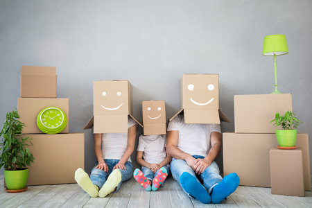 Photo pour Happy family playing into new home. Father, mother and child having fun together. Moving house day and think outside the box concept - image libre de droit