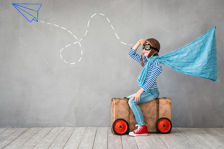 Foto de Child pretend to be pilot. Kid having fun at home. Summer vacation and travel concept - Imagen libre de derechos