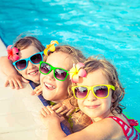 Photo for Happy children in the swimming pool. Funny kids playing outdoors. Summer vacation concept - Royalty Free Image