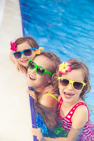 Foto de Happy children in the swimming pool. Funny kids playing outdoors. Summer vacation concept - Imagen libre de derechos
