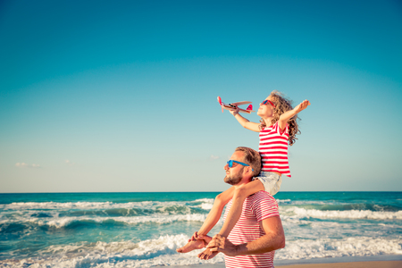 Foto de Happy family on the beach. People having fun on summer vacation. Father and child against blue sea and sky background. Holiday travel concept - Imagen libre de derechos