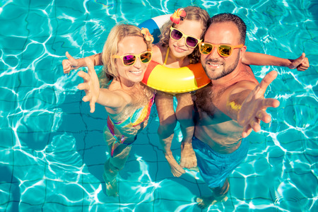 Foto de Happy family having fun on summer vacation. Father, mother and child playing in swimming pool. Active healthy lifestyle concept - Imagen libre de derechos