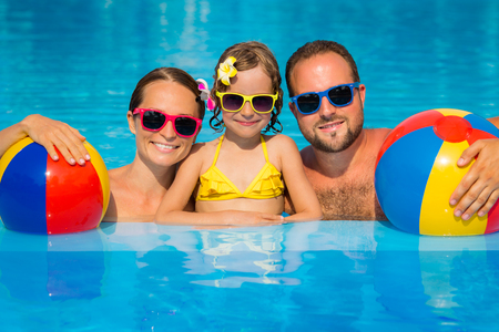 Photo pour Happy family having fun on summer vacation. Father, mother and child playing in swimming pool. Active healthy lifestyle concept - image libre de droit