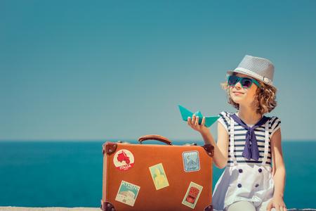 Photo pour Happy child with vintage suitcase. Kid having fun on summer vacation. Travel and adventure concept - image libre de droit