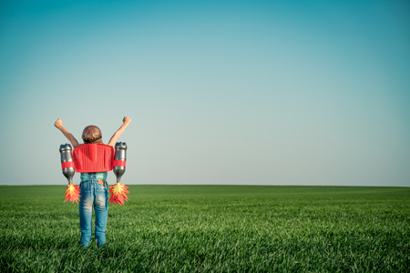Foto de Kid with jet pack outdoor. Child playing in green spring field. Success, imagination and innovation technology concept. Summer travel and adventure - Imagen libre de derechos
