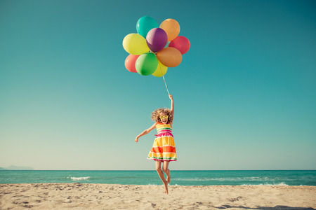 Photo pour Happy child jumping with colorful balloons on sandy beach. Portrait of funny girl against blue sea and sky background. Active kid having fun on summer vacation. Freedom and imagination concept - image libre de droit