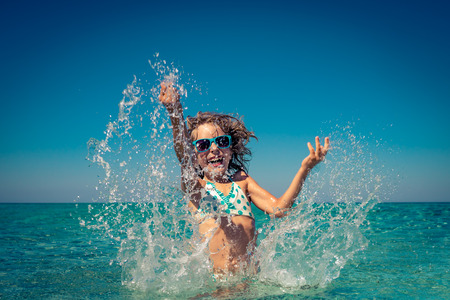 Foto de Happy child playing in the sea. Kid having fun at the beach. Summer vacation and active lifestyle concept - Imagen libre de derechos