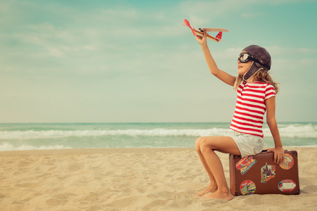 Photo for Happy child playing with toy airplane against sea and sky background. Kid pilot having fun outdoor. Summer vacation and travel concept. Freedom and imagination - Royalty Free Image