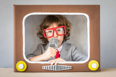 Photo pour Child playing with cardboard box TV. Kid having fun at home. Communication concept - image libre de droit