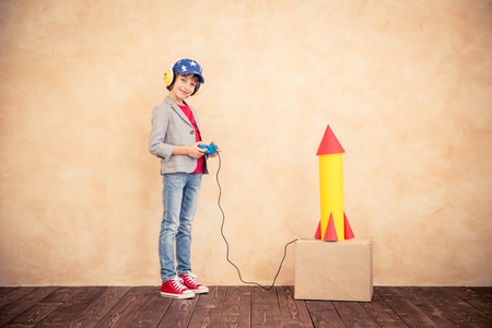 Photo pour Kid with jet pack. Child playing at home. Success, imagination and innovation technology concept - image libre de droit