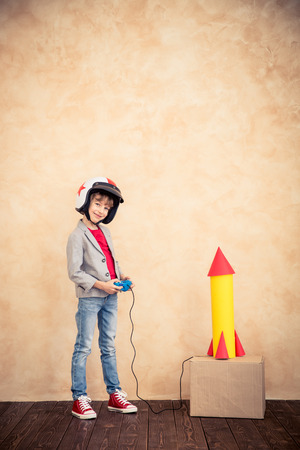 Photo pour Kid with cardboard rocket. Child playing at home. Success, imagination and innovation technology concept - image libre de droit