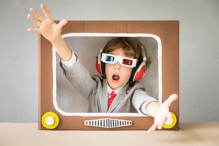 Photo pour Child playing with cardboard box TV. Kid having fun at home. Video blogging concept - image libre de droit