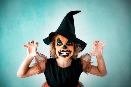 Foto de Funny child dressed witch costume. Kid painted terrible pumpkin. Halloween autumn holiday concept - Imagen libre de derechos