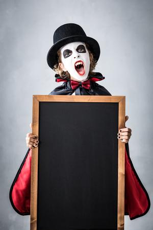 Foto de Funny child dressed Halloween costume. Kid painted terrible vampire holding banner blank. Autumn holiday concept - Imagen libre de derechos